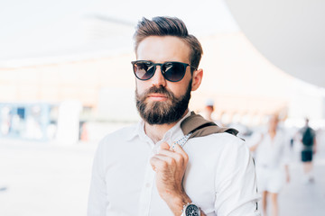 Half length of young handsome modern businessman wearing sunglasses posing in the city backlight, looking at camera - business, success concept