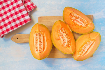 Cantaloupe melon slices on rustic wooden table, top view