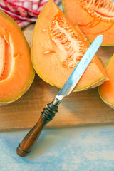 Cantaloupe melon slices and knife on rustic wooden table