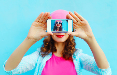 Woman makes self-portrait on smartphone view screen over colorfu