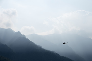 Helicopter flying in the misty mountains