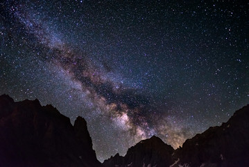 The colorful glowing core of the Milky Way and the starry sky captured at high altitude in summertime on the Alps. Scenic snowcapped mountain silhouette.