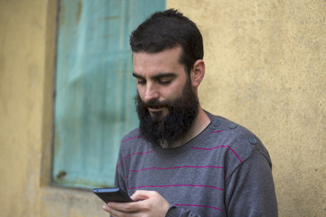 Bearded young man looking at mobile and wall of a cottage in the background.
