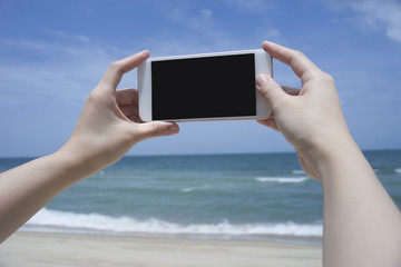 Close up of woman's hand holding smartphone, mobile, smart phone over blurred beautiful blue sea to take a photo of the sea,phone with black screen