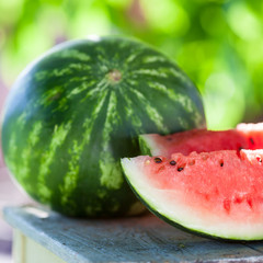 Fresh watermelon cut on a wooden table in the garden. Healthy raw diet food.