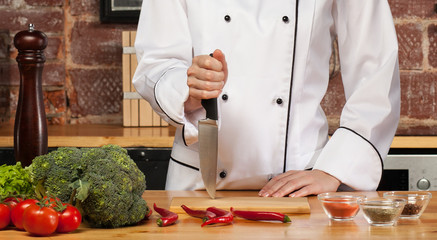 cook hand plunges knife in cutting board
