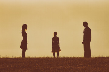 Silhouette of a angry husband and wife  on each other looking at their daughter and waiting for her to choose between them.