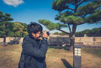 Asian man taking photo in Japanese garden
