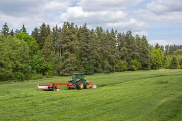 Image of a tractor on meadow. Early grass cutting for BIOGAS production