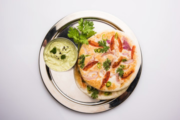 south indian food, two uttapam with coconut chutney in white ceramic plate with coriander leaf, closeup