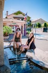 Femme et fillette, bain de pieds dans la fontaine de Cairanne