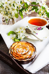 Apple shaped roses pie and cup of tea on the serving tray