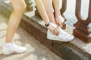 Woman hands with black fitness bracelet adjusts laces on white sneakers. On the street, on the parapet of the river. Sunny effect.