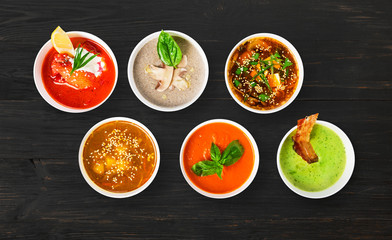 Variety of soups at black wood, top view