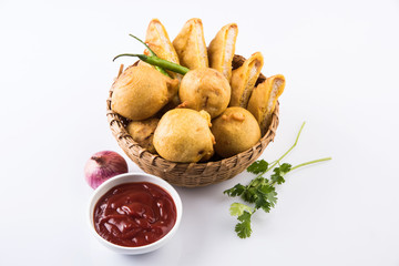 black gram or urad dal vada or pakoda or aalu bonda, aalu bonde with coconut and pudina chutney, isolated on red background, top view