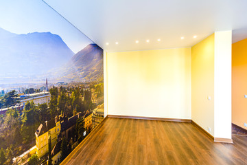 Interior of an empty room in orange tones with a panorama photo wall mural Merano (South Tyrol, Italy)