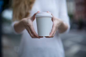Two female hand holding paper cup