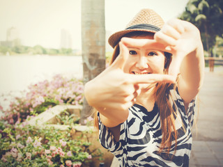 Beautiful Asian girl using hands framing for taking photos in outdoor scene - vintage tone