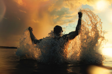 Strong and athletic man jumps out of the water at sunset, flying a lot of splashing Wall mural