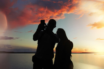 A man and a woman at sunset makes a photo (selfie) at the lake