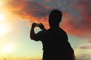 Strong man with a backpack takes the photo of a beautiful sunset on a smartphone