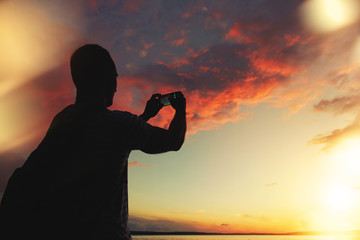 A man takes a photo of the sunset on your smartphone