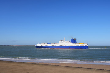 Blue cargo ship sailing to Antwerp port by the coast of Vlissingen, Netherlands