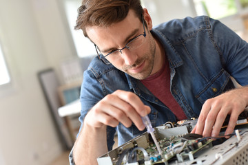 Repairman fixing tv set