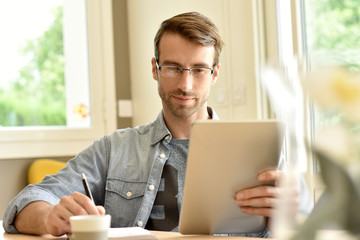 man at home working on digital tablet