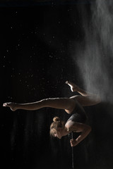 Gymnastic woman handstand on equilibr while sprinkled flour