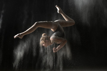 Woman gymnast handstand on equilibr while sprinkled flour