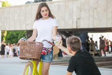 Beautiful girl on bike sells cocktail guy