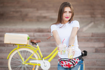 Girl holding a cocktail on the background of the bike