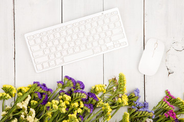 Wireless slim keyboard, mouse and colorful flowers on white desk