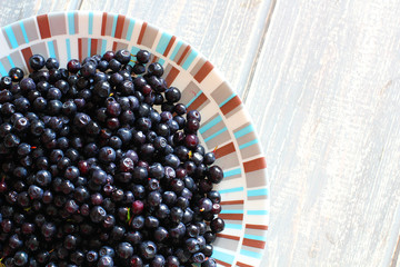 Bilberries in white plate on wooden grey desk.