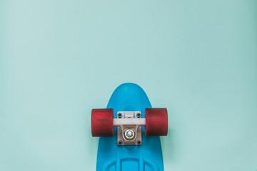 Blue Skateboard on blue background. Flat lay fashion set.