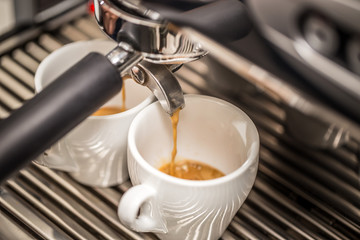 Espresso machine pouring coffee in white cups