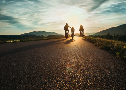Cyclists family traveling on the road at sunset
