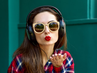Beautiful smiling woman with headphones listens to music. Blowin