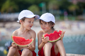 Two little children, boy brothers, eating watermelon on the beac