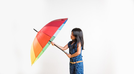 Indian small girl with multicolored umbrella, isolated over white