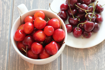 Cherries in white cup on wooden grey desk.