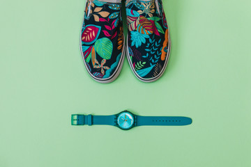 Flat lay fashion set: colored slippers shoes with palm and flowers print and blue watch on pastel background. Top view.