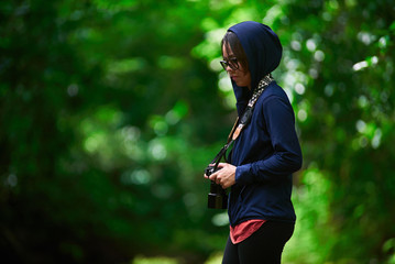 alone girl taking photo with digital camera in the forest