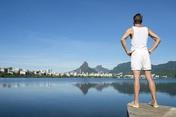 Athlete in white sport uniform standing with hands on hips in front of Rio de Janeiro, Brazil skyline at Lagoa Rodrigo de Freitas Lagoon