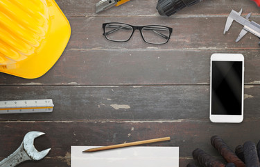 Construction site table with free space for text. Smart phone, helmet, paper, pencil, ruler, glasess beside.