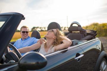 Glückliches Liebespaar im Cabrio - Mann und Frau fahren im Auto