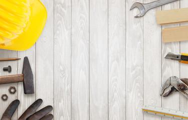 Construction worker tools on wooden table. Helmet, hammer, gloves, pencil pliers, scalpel beside.