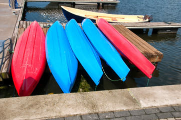 Colorful small boats stacked along wooden pier