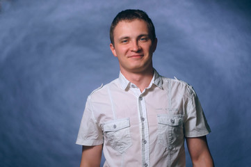 Portrait of smiling happy young man on dark background